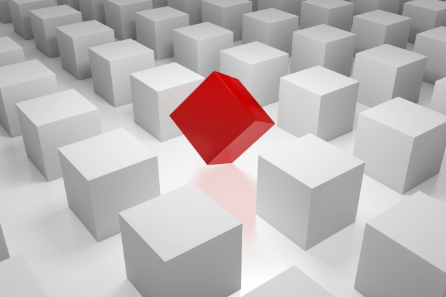 In an ordered field of white cubes, a red, skewed cube breaks the pattern