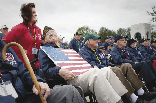 A group of veterans, seated in wheelchairs, visit the World War II memorial.
