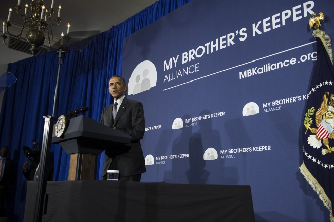 President Barack Obama at a podium in front of a My Brother's Keep Alliance backdrop.