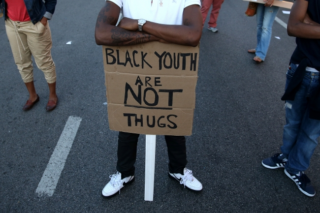 A young man holds a sign that reads 'Black youth are not thugs.'