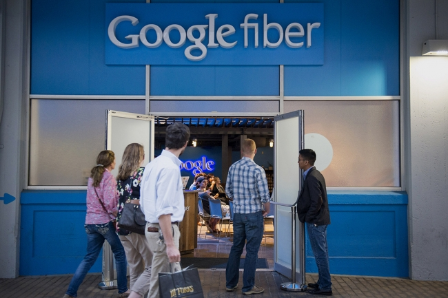 People walk into a Google Fiber store.