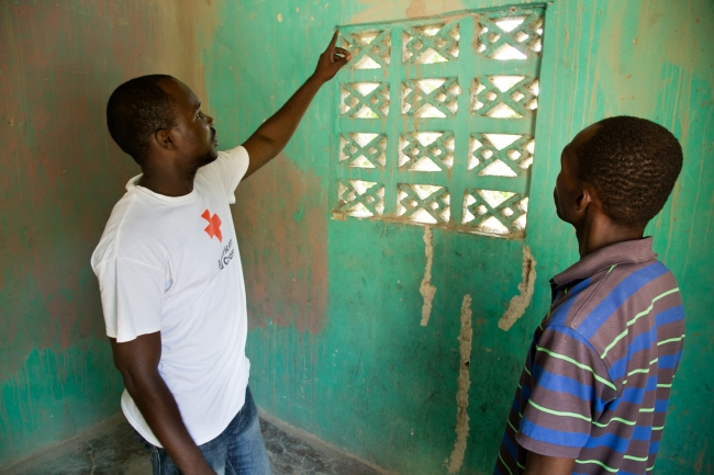 Homeowner Reynald Gue (right) talks to American Red Cross staff member Garry Calixte (left) inside Reynald's house in the Carrefour area of Port-au-Prince, Haiti.